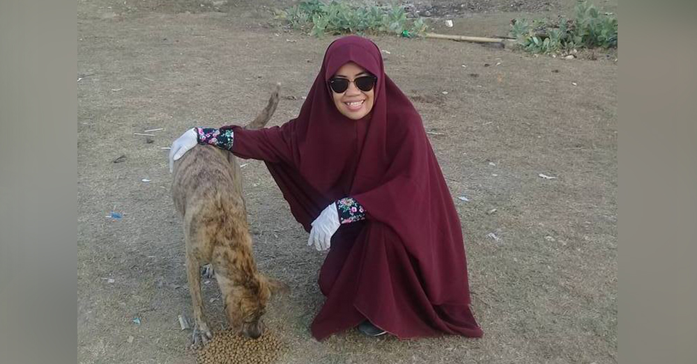 Source: Facebook/Desy Marlina Desy Marlina and one of the dogs she's helped sterilize and care for.