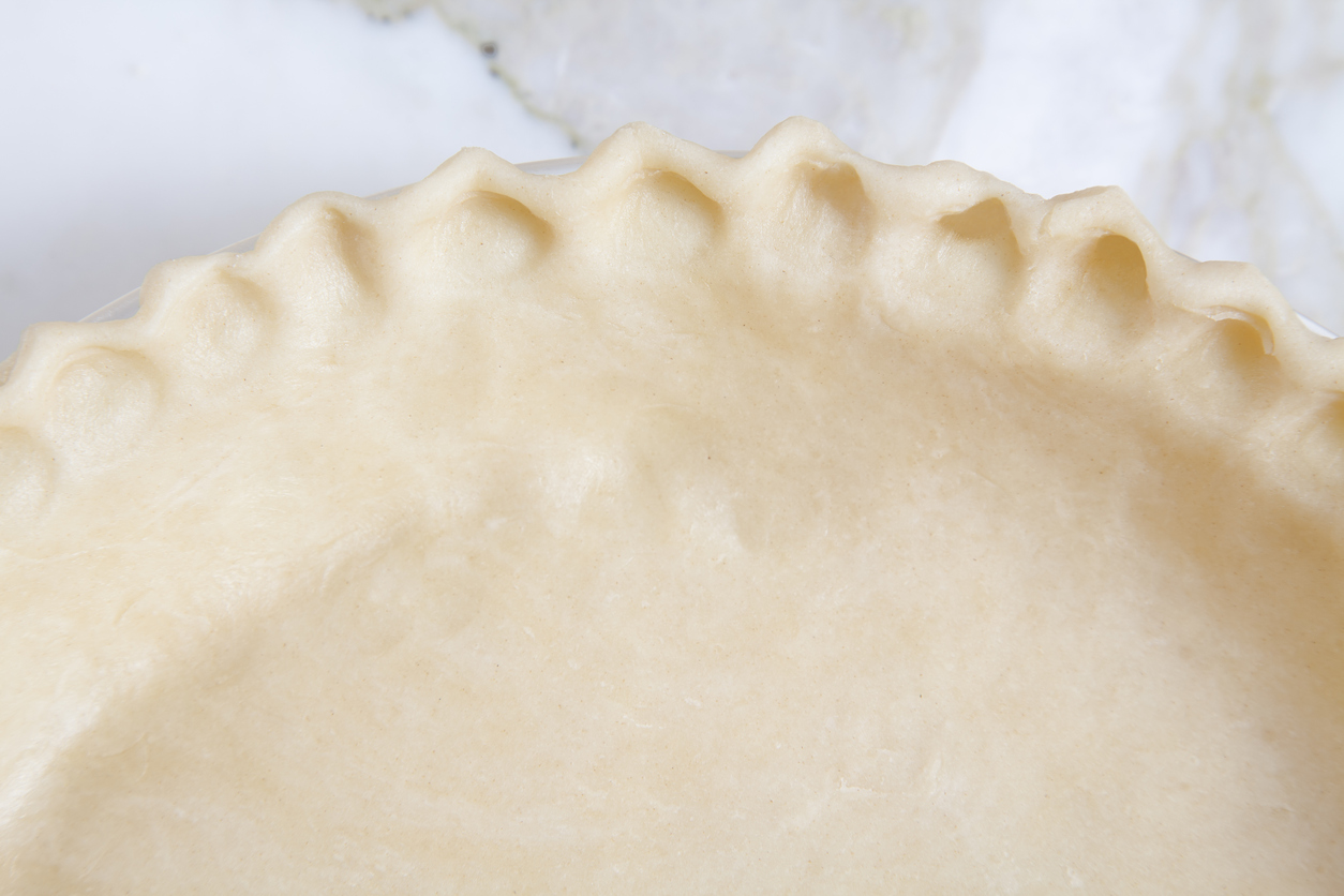 Fluted or crimped pie crust ready to bake on a marble counter top.
