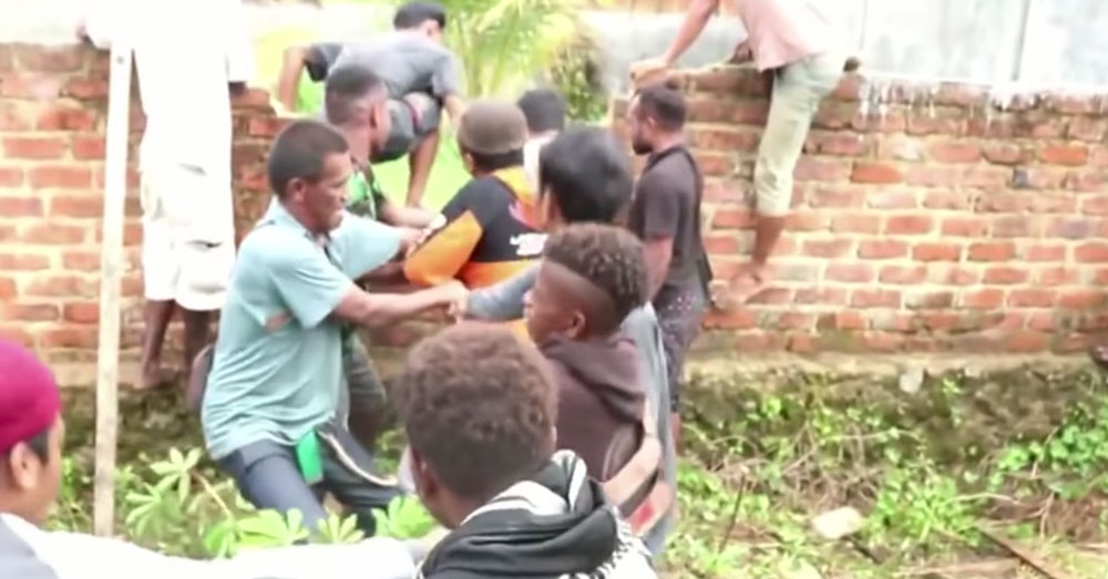 Source: YouTube/TIME Sorong villagers overtake the sanctuary wall.