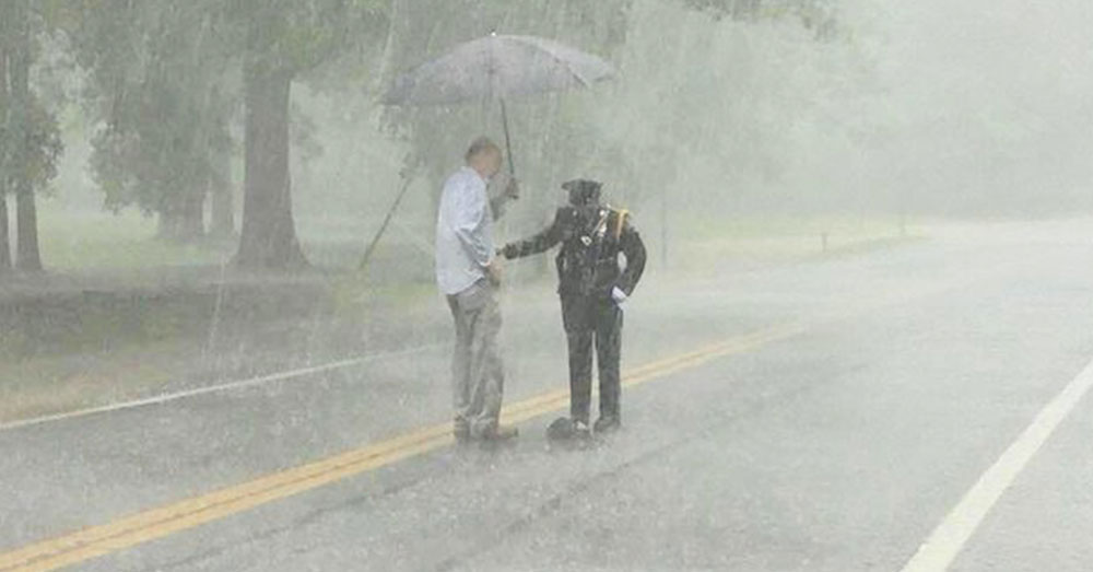 Source: InspireMore Kevin Hammett brings the officer an umbrella.