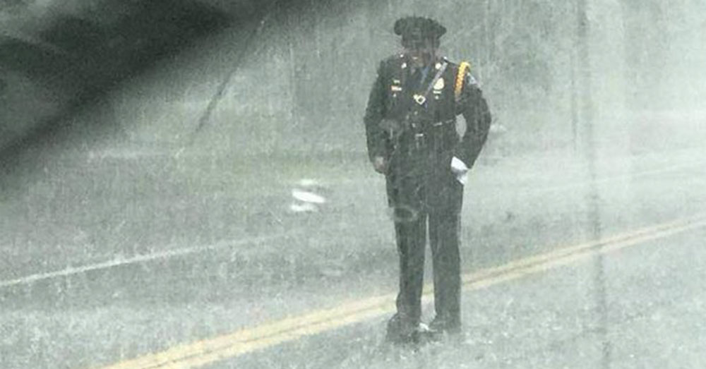 Source: InspireMore An officer stands in the rain, grinning.