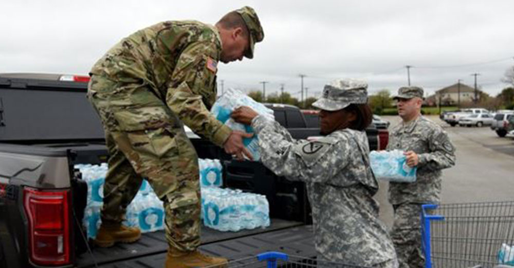 Source: Department of Defense Texas Army National Guard members Maj. George Hurd, left, Staff Sgt. Erdoo Thompson, center, and 1st Lt. Matthew Verdugo, all from the 136th Maneuver Enhancement Brigade, load bottled water in Round Rock, Texas, in preparation for Hurd's convoy to Flint, Michigan, in 2016.