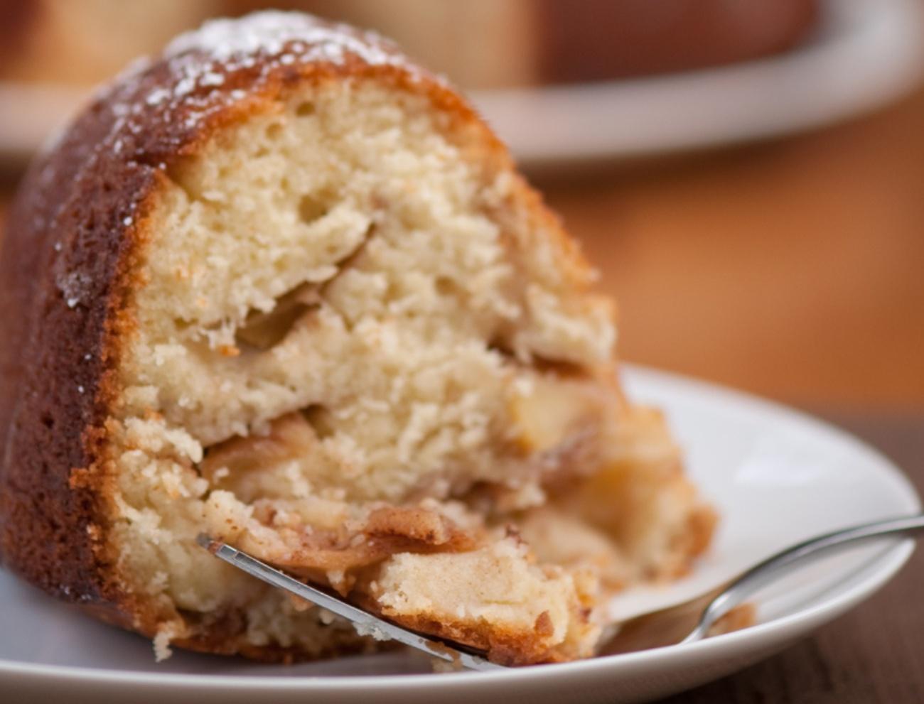Slice of apple bundt cake with more dessert in background