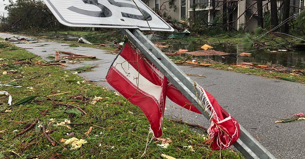 Source: Twitter/KDFiscus A ripped flag wrapped around a road sign, bent by the winds of Hurricane Michael.