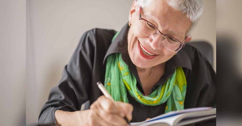 A woman smiling as she handwrites a message on a card