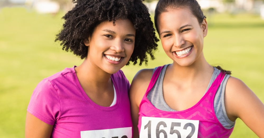 Two women athletes smiling and posing for the camera with their arms around each other