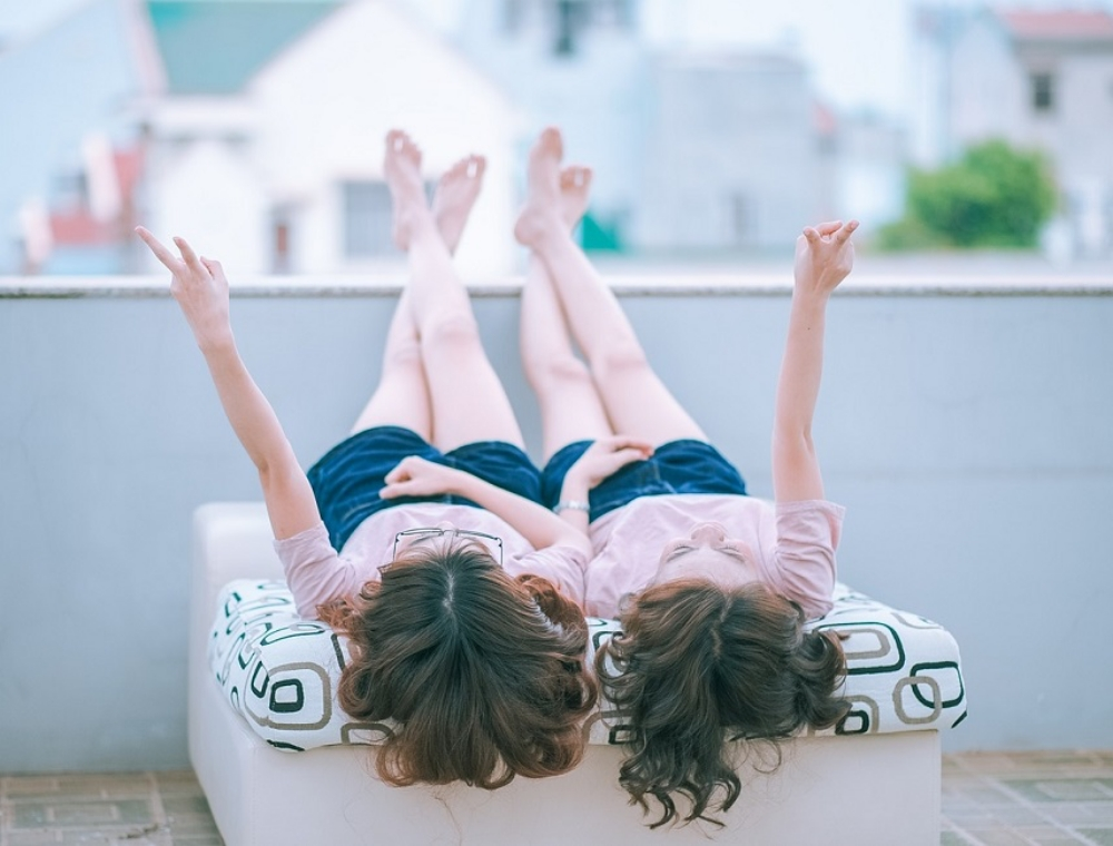 adolescent twin girls lying on a bed