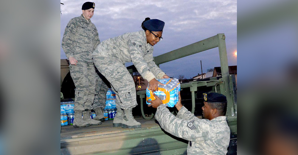 Staff Sgt. Kendall Iverson, 78th Security Forces Squadron flight chief, hands a case of water to entry controllers Airmen First Class Shaquan Roberts and Aleia Moss, Feb 25, 2016. The unit collected five tons of bottled water to help Flint residents with their water crisis.