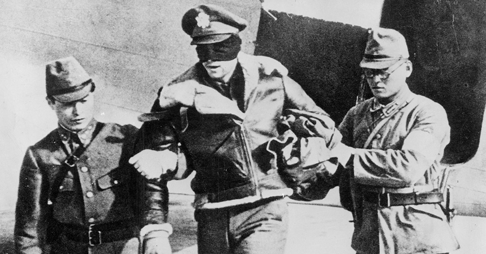 U.S. Army Air Force Lt. Robert L. Hite, blindfolded by his captors, is led from a Japanese transport plane after he and the other seven flyers were flown from Shanghai to Tokyo.