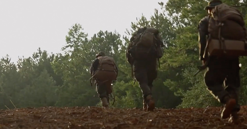 Marines go on a ruck through the woods.