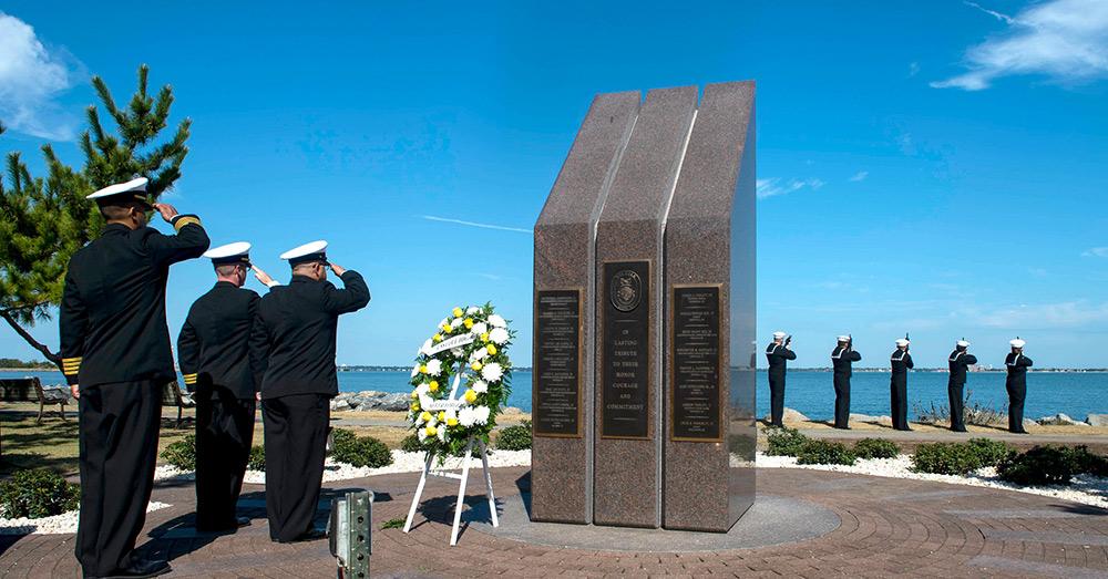 Sailors render honors at the USS Cole Memorial.