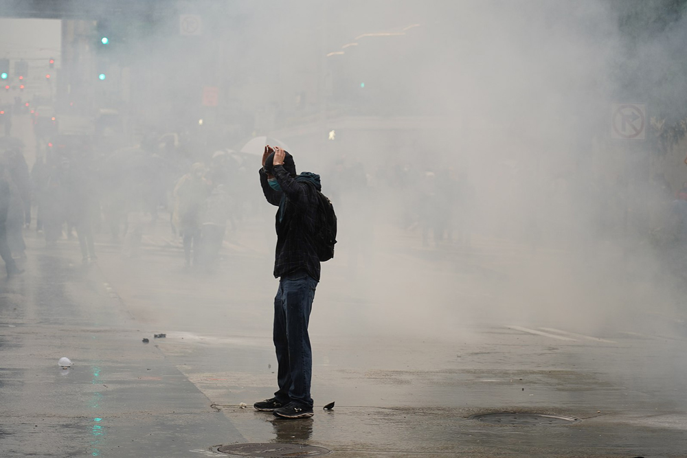 A protester is surrounded by tear gas.