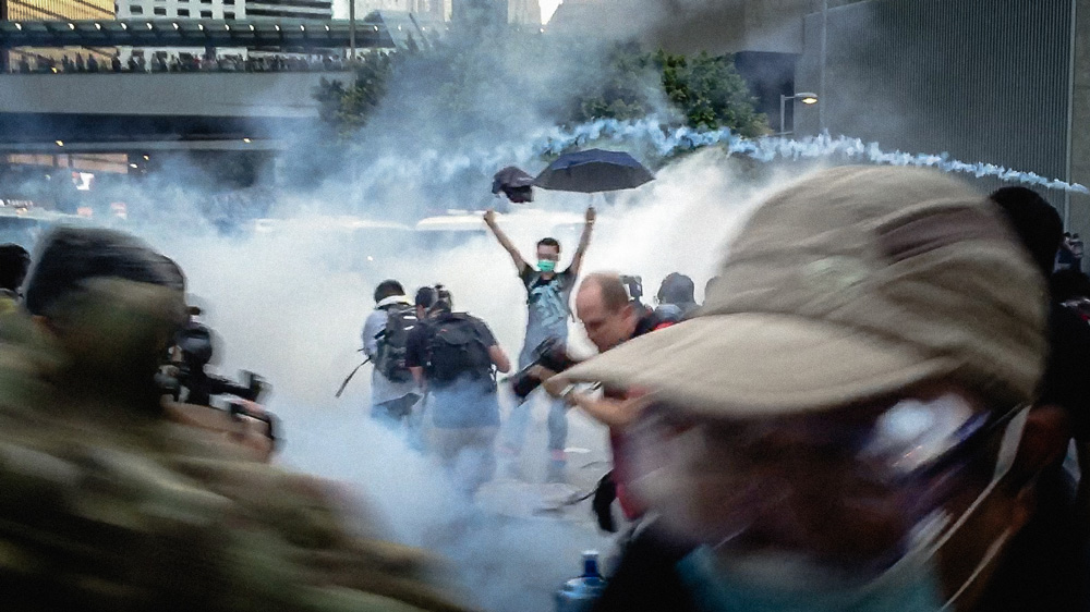 A protester holds an umbrella in the midst of tear gas.