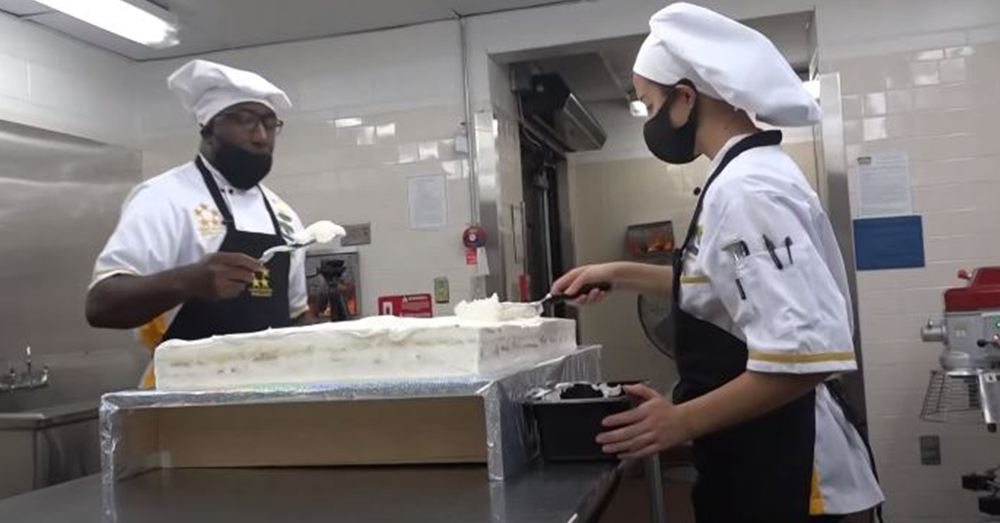 Two Navy sailors work on a special cake in the galley.