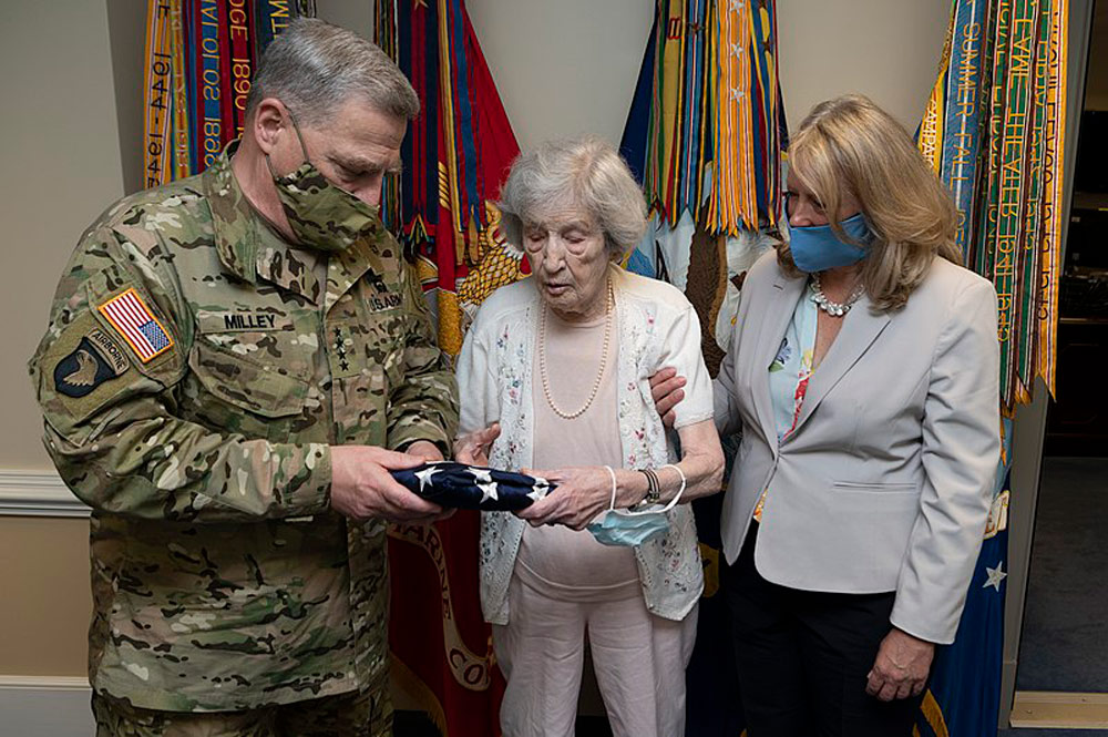Chairman of the Joint Chiefs of Staff, Gen. Mark A. Milley and his wife Hollyanne present World War II veteran Lt. Regina Benson with an American flag that was flow over the Pentagon, July 10, 2020.