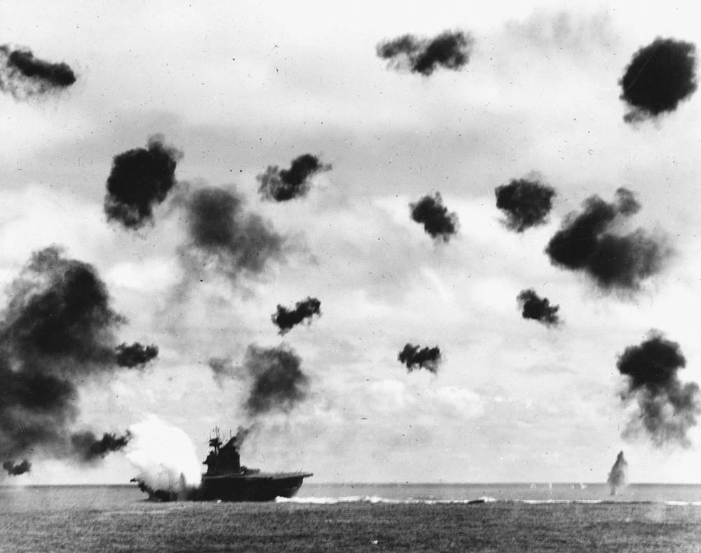 USS Yorktown (CV-5) is hit on the port side, amidships, by a Japanese Type 91 aerial torpedo during the mid-afternoon attack by planes from the carrier Hiryu, in the Battle of Midway.