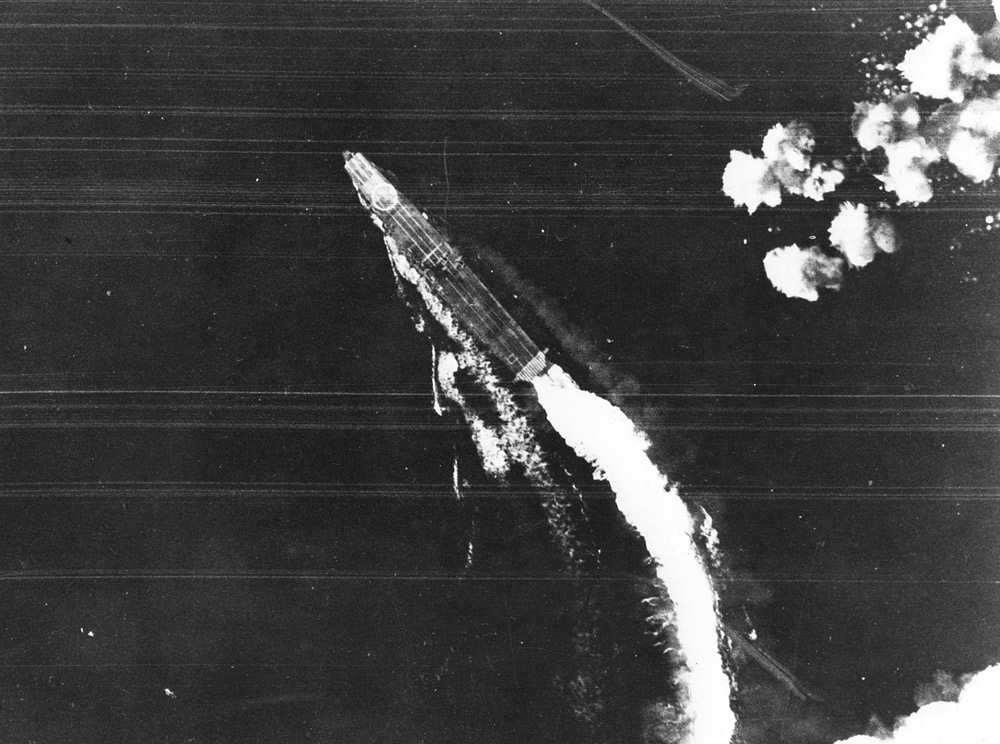 The Japanese aircraft carrier Hiryu maneuvers to avoid bombs dropped by USAAF Boeing B-17E Flying Fortress bombers during the Battle of Midway.