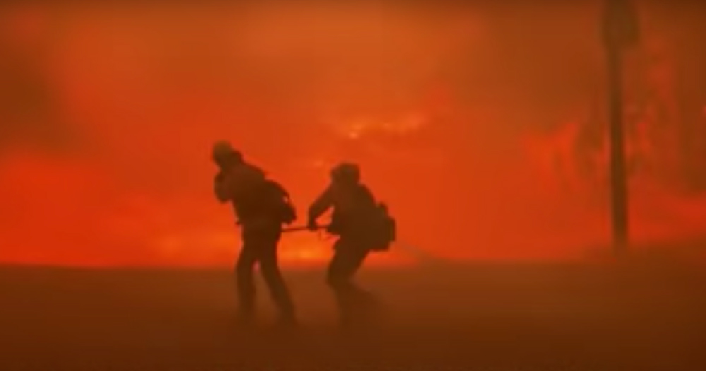 Firefighters are silhouetted by smoke and the red light of the Bond Fire.