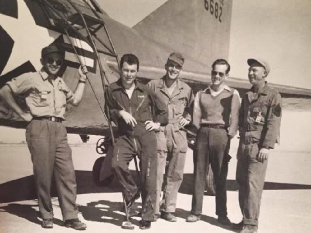General Chuck Yeager leans against the ladder (second from left).