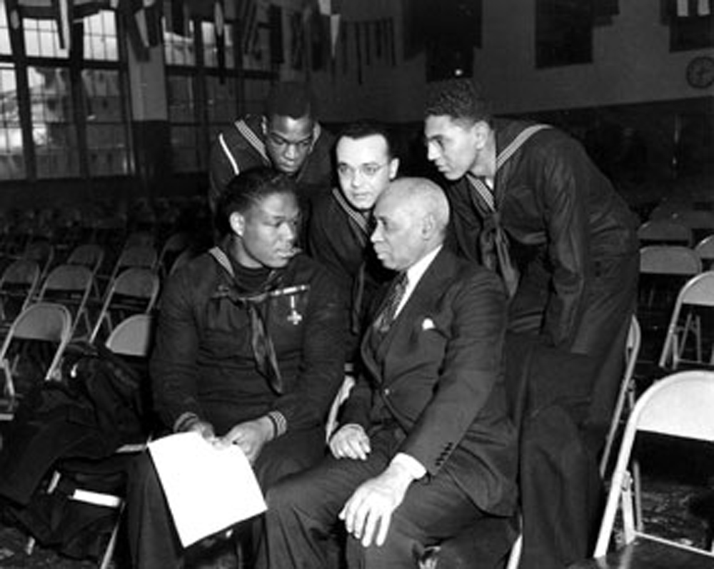 Miller speaking with sailors and a civilian at Great Lakes Naval Training Station, January 7, 1943.