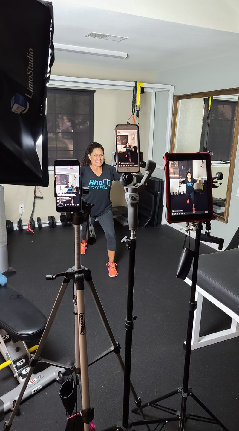 Rhonda Murphy demonstrating a workout in front of three different devices for a livestream