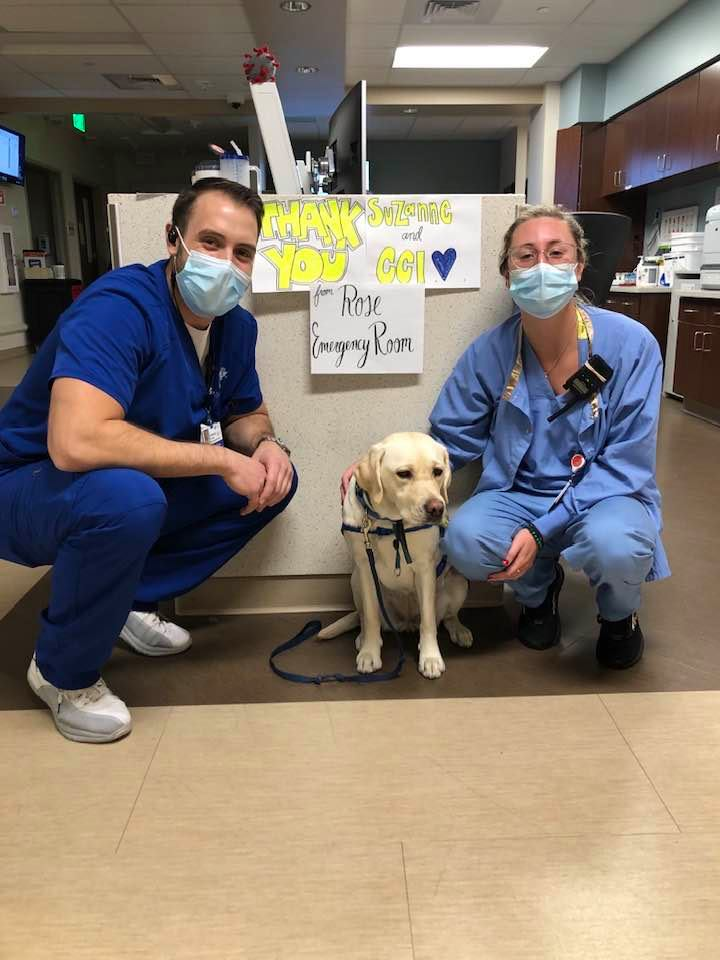two hospital staff members are crouched next to service dog, Wynn, with a sign that says