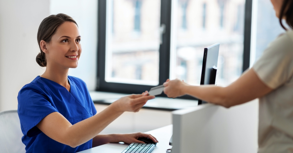 Female patient hands healthcare insurance card to receptionist at doctor's office