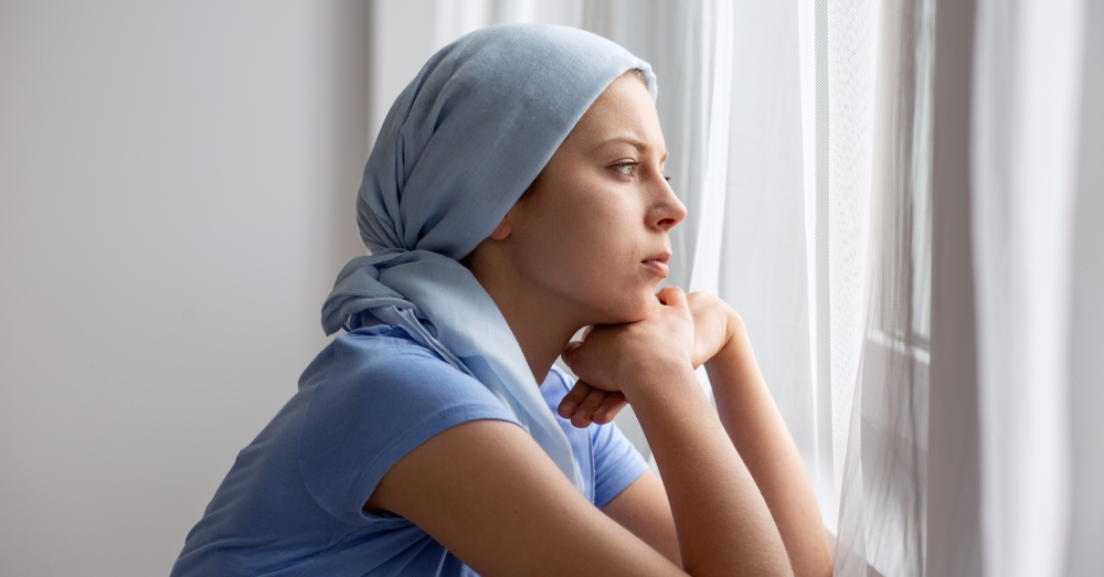 Young woman with ovarian cancer and headscarf looks thoughtfully out the window