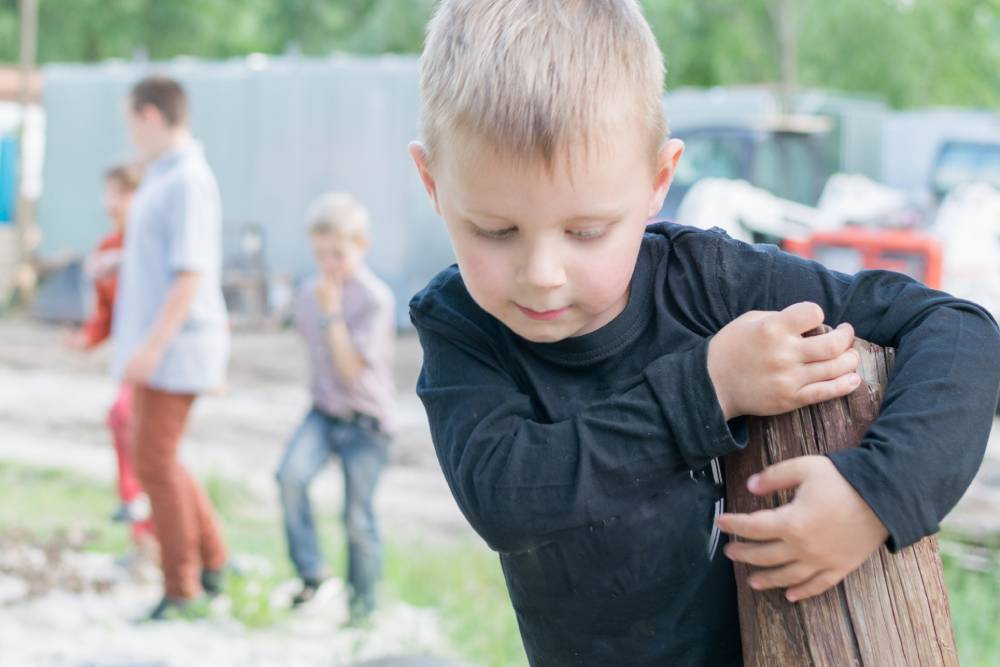 Boy playing by himself away from group