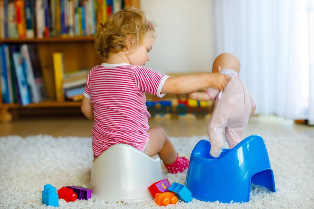 Little girl and potty training doll