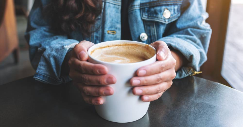 woman holding large cup of coffee